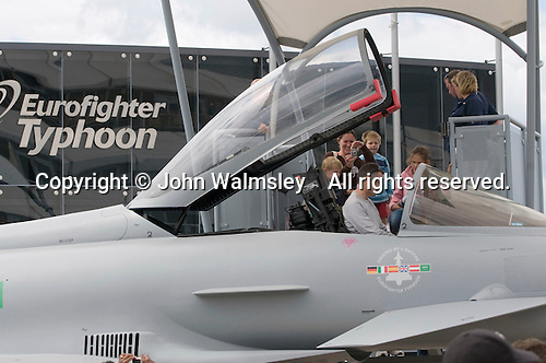 A father sits in the cockpit of a Eurofighter Typhoon at the Farnborough International Airshow .