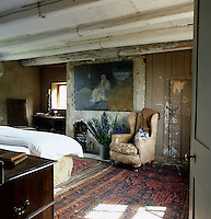 A modern painting hangs above a shabby armchair and a bucket filled with delphinums at one end of the master bedroom