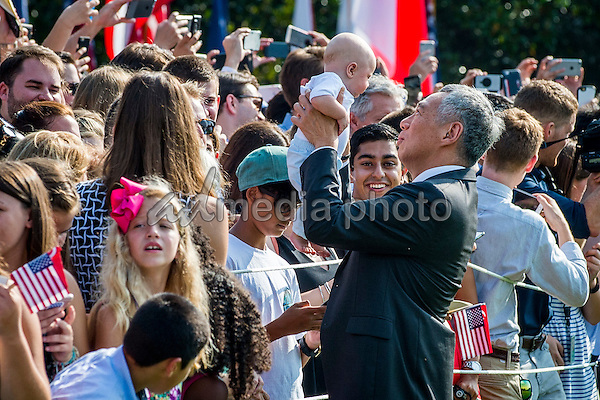 Prime Minister Lee Hsien Loong of Singapore lifts up a baby while greeting guests during official welcoming ceremonies on the South Lawn of the White House in Washington, DC on August 2, 2016. Lee is on a State Visit to the United States. Photo Credit: Pete Marovich/CNP/AdMedia