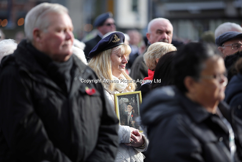 Pictured: A woman holds a picture of a deceased serviceman Friday 11 November 2016<br />
