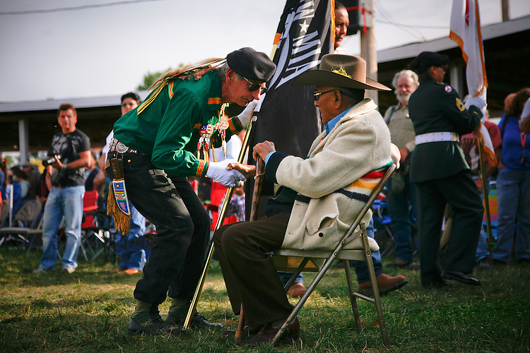 A flag bearer greets a Crow Elder during the Grand Entry.