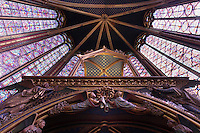 View from below of the choir with the reliquary in the foreground, upper chapel of La Sainte-Chapelle (The Holy Chapel), 1248, Paris, France. The upper chapel has four bays and a seven section choir. In the choir, the windows have only two lancets. Fifteen huge mid-13th century windows fill the nave and apse. La Sainte-Chapelle was commissioned by King Louis IX of France to house his collection of Passion Relics, including the Crown of Thorns and is considered among the highest achievements of the Rayonnant period of Gothic architecture. Picture by Manuel Cohen
