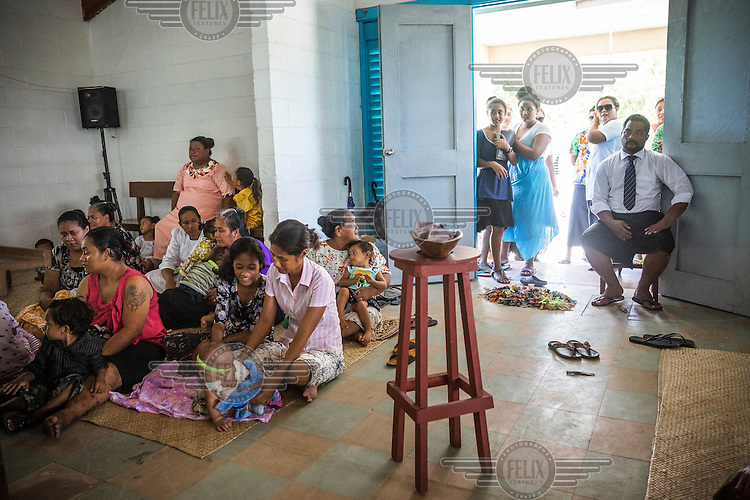 People during the Sunday service at the Protestant Church of Funafuti. After Cyclone Pam hit the country in March 2015, Tuvaluans spent time praying for those who lost their homes. The Cyclone hit several atolls of the Central and Northern Tuvalu archipelago. According to Tuvalu's Prime Minister Enele Sopoaga, an estimated 45% of the nation's nearly 10,000 people were displaced.