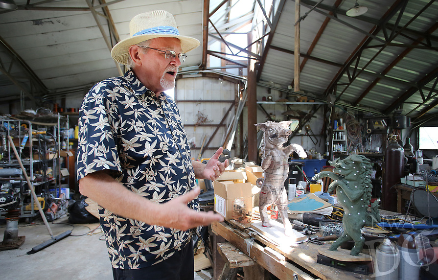 NWA Democrat-Gazette/DAVID GOTTSCHALK Cliff Slinkard, owner of Hogeye Inc., describes the building of models Wednesday, June 6, 2018, of a 25 foot tall boar at the studio of artist Eugene Sargent in rural Washington County. Sargent was commissioned by Slinkard to design and build the boar that will be installed Sunday, June 10, 2018 and a five foot tall base at the company office at 4148 West Matin Luther King Jr. Boulevard in Fayetteville.