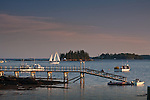 A schooner passes two lighthouses at sunset in Boothbay Harbor, ME, USA