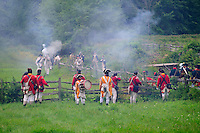 British redcoat soldiers of the Tenth Regiment of Foot, with drummers, and Loyalist King's Rangers, engage the Continental Army at a Revolutionary War encampment, Old Sturbridge Village, Massachusetts, USA.