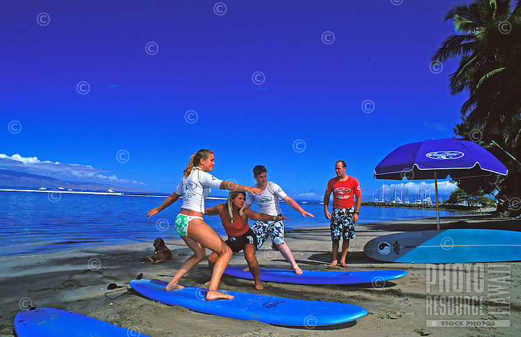 Tourists being taught how to surf for the first time by former World Pro Surfing Champion Nancy Emerson in Lahaina. Emerson has been teaching for over 25 years. Lessons here are being taught just south of Lahaina Harbor.