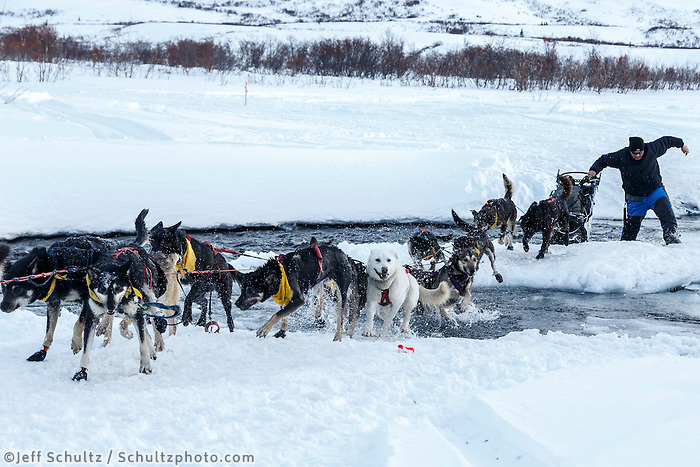 John Baker crosses the open water of the Happy River in Ptarmigan Valley on the way to Rohn from the Rainy Pass checkpoint during Iditarod 2016.  Alaska.  March 07, 2016.  <br /> <br /> Photo by Jeff Schultz (C) 2016 ALL RIGHTS RESERVED