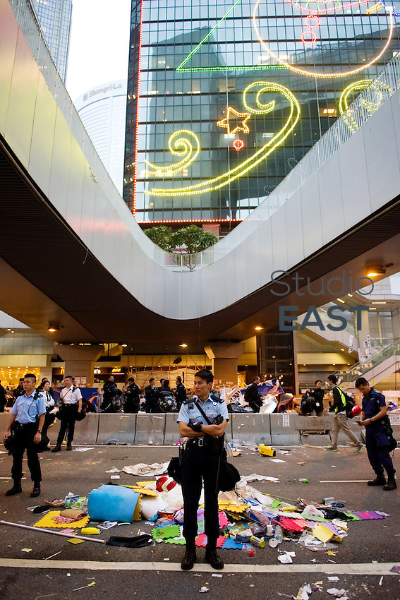 HONG KONG - DECEMBER 11: A policeman stands in front of rubbish remaining after the clearance of Occupy Central Pro-democracy camp in Admirality, on December 11, 2014 in Hong Kong, Hong Kong. (Photo by Lucas Schifres/Getty Images)