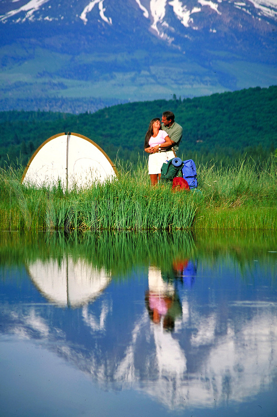 couple embracing next to camp tent showing reflection in lake. couple. Mt. Shasta California USA.