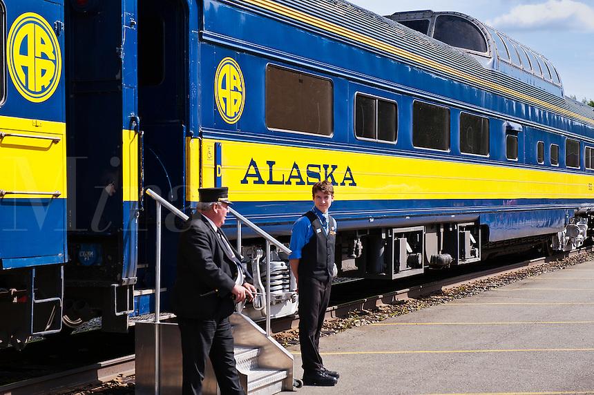 Conductor and clerk await passangers aboard an Alaska Railroad train, USA