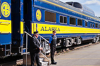 Conductor and clerk await passangers aboard an Alaska Railroad train, USA