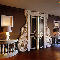 An ornate carved door frame is flanked by a matching pair of console tables in the drawing room