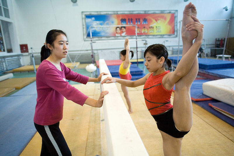 A coach watches as young gymnast Jin Yang stretches her legs in an afternoon training session of the Beijing Gymnastic team.