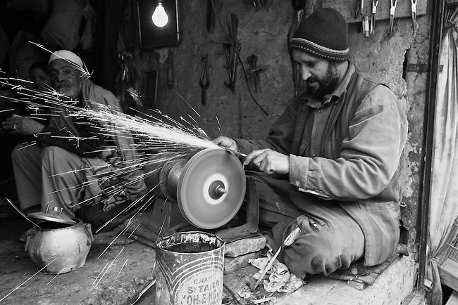 A man sharpens a knife blade on an electric grinding wheel in the central market of Kabul, Afghanistan. Despite the ever-present mud and miserable winter weather, the market bustles daily with commerce of all kinds. Taliban attacks in the Afghan capital have so far been infrequent, and as life goes on at a normal pace, the war often seems far away. Feb. 3, 2009.