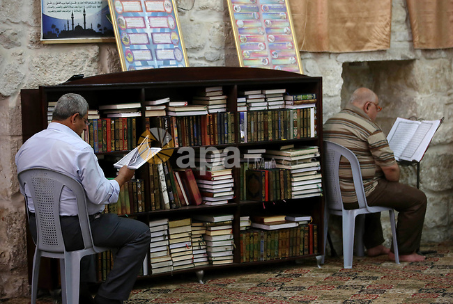 Palestinians read copies of the Koran, Islam's holiest book, on the Muslim holy fasting month of Ramadan at the al-Hanbali mosque in the Old City of the West Bank town of Nablus on May 28, 2017. Ramadan is sacred to Muslims because it is during that month that tradition says the Koran was revealed to the Prophet Mohammed. The fast is one of the five main religious obligations under Islam. More than 1.5 billion Muslims around the world will mark the month, during which believers abstain from eating, drinking, smoking and having sex from dawn until sunset. Photo by Ayman Ameen