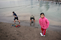 CHINA. Sichuan Province. Chongqing. Children playing in The Yangtze River which is at its lowest level in 150 years as a result of a country-wide drought. Chongqing is a city of over 3,000,000 people, famed for being the capital of China between 1938 and 1946 during World War II. It is situated on the banks of the Yangtze river, China's longest river and the third longest in the world. Originating in Tibet, the river flows for 3,964 miles (6,380km) through central China into the East China Sea at Shanghai.  2008.