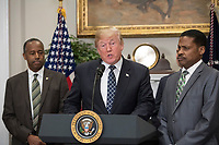 United States President Donald J. Trump makes remarks prior to signing a proclamation to honor Dr. Martin Luther King, Jr. Day in the Roosevelt Room of the White House in Washington, DC on Friday, January 12, 2018.  Looking on from left is US Secretary of Housing and Urban Development Ben Carson and looking on from right is Isaac Newton Farris, Jr., Nephew of Martin Luther King Jr.<br /> CAP/MPI/RS<br /> &copy;RS/MPI/Capital Pictures