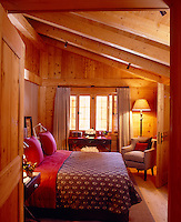 The cosy chalet bedroom has a comfortable bed covered with a patterned quilt