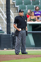 Home plate umpire Zach Tieche gets some new baseballs during the South Atlantic League game between the Augusta GreenJackets and the Kannapolis Intimidators at CMC-NorthEast Stadium on July 31, 2014 in Kannapolis, North Carolina.  The Intimidators defeated the GreenJackets 4-3.  (Brian Westerholt/Four Seam Images)