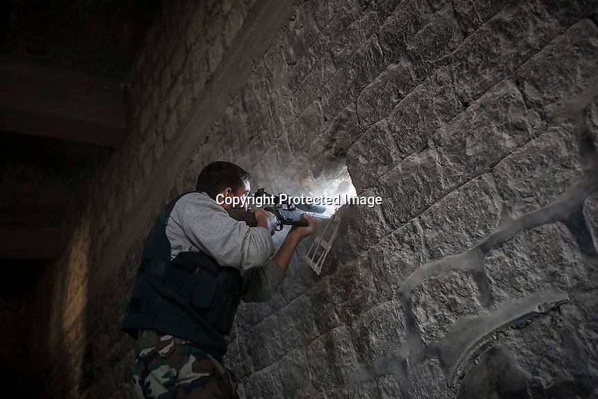 In this Sunday, Nov. 04, 2012 photo, a rebel sniper aims fire through a hole in the wall that overlooks a position held by Syrian troops loyal to President Bashar Al-Assad hidden in a building as they attempt to gain terrain forward the rebel lines during heavy clashes in the nearby Qastal Al-Harami battlefield in the Jdeide district of Aleppo, the Syrian's largest city. (AP Photo/Narciso Contreras).