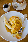 Celebrity chef Bill Granger owns Bill's Cafe in the Darlinghurst neighborhood of Sydney, NSW features a large communal table.  Pictured here are the ricotta stuffed banana pancakes with a cappuccino.