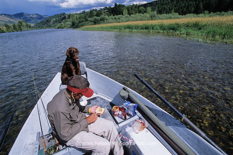 081500-D. An angler in a drift boat fixes a peanut butter and jelly sandwich for lunch while his chocolate Labrador retriever licks her chops during a fishing trip on the South Fork of the Snake River, Idaho (original image is 35mm transparency).