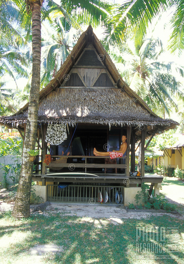 Surfers relaxing in traditional thatched hut at Sagana Resort, in remote Siargao Island, Philippines