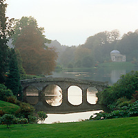 A misty view across the expansive lake at Stourhead in Wiltshire, with its romanticised neo-classical architecture