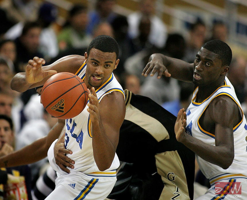 UCLA Bruins Josh Shipp,left, and Alfred Aboya, right, grab a loose ball away from Oakland Grizzlies Derick Nelson,center, during 1half action NCAA basketball at Pauley Pavilion, December 16, 2006.