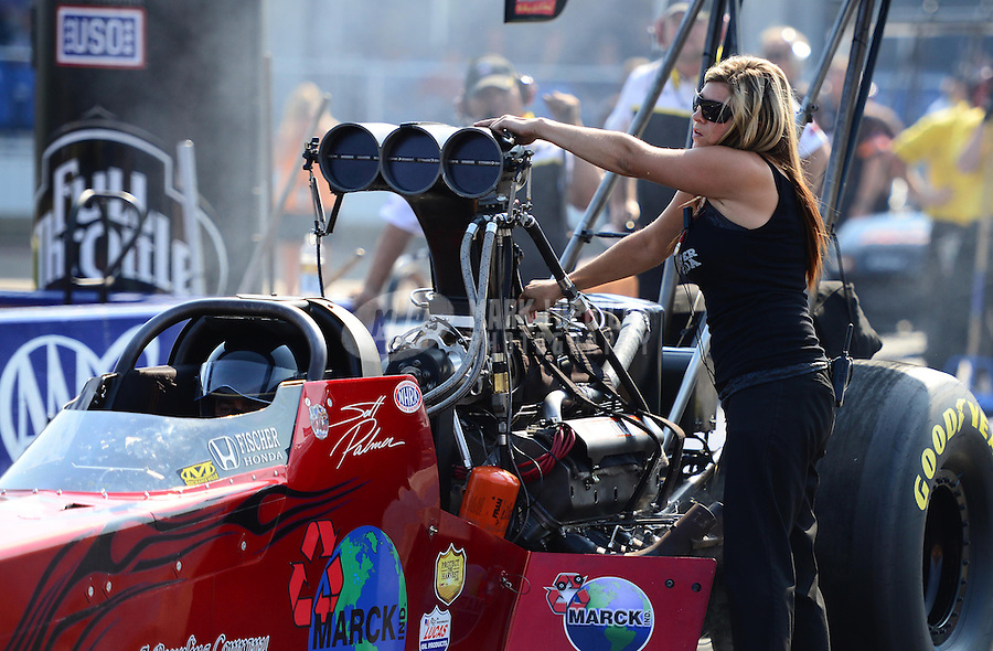Sept. 21, 2012; Ennis, TX, USA: NHRA crew member Ashley Fye makes adjustments to the car  of top fuel dragster driver Scott Palmer during qualifying for the Fall Nationals at the Texas Motorplex. Mandatory Credit: Mark J. Rebilas-