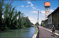 Cassano d'Adda (Milano). Pista ciclabile lungo il Naviglio Martesana e una torre dell'acqua --- Cassano d'Adda (Milan). Bicycle path along the Naviglio Martesana canal and a water tower