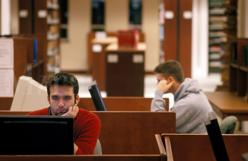 College students working in library on computers with flat panel display screens.