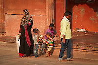 The glow of red sandstone surround this visiting family at Jama Masjid Mosque in Delhi.