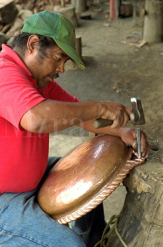 Copper worker adding decorative scrollwork to edge of copper tray with hammer and chisel. Santa Clara del Cobre Michoacan Mexico.