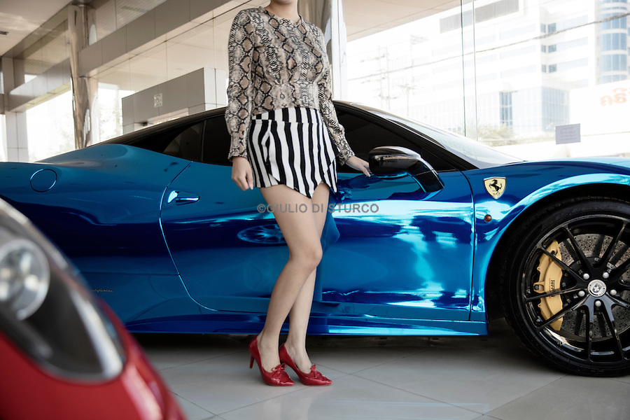 LAOS, NOVEMBER 2015<br />Downtown Vientiane, a young woman looks at a Ferrari in a dealership across from the stock exchange building, a sign of the recent boom in economy for one of the last communist countries. Vientiane, Laos, 2015.<br />@Giulio Di Sturco