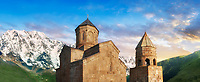 Pictures & images of Gergeti Holy Trinity (Tsminda Sameba) Georgian Orthodox and Apostolic Church and bell tower, 14th century, Gergeti, Khevi province, Georgia (country). At Sunset.