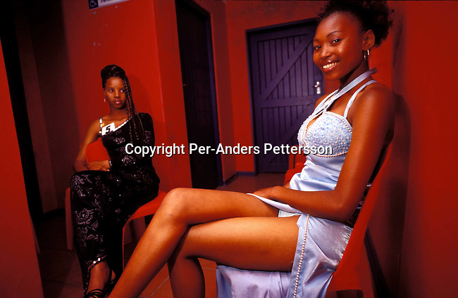 digefas00130 Fashion. Nokybonga Maxhwee, age 20, (right) together with a fellow woman backstage during a Miss Khayelitsha beauty contest  on August 12, 2001 in Site C Khayelitsha, a township about 35 kilometers outside Cape Town, South Africa. Acacia was going to be married a few months later but the wedding was postponed because of a dead relative.  Khayelitsha is one of the poorest and fastest growing townships in South Africa. People usually come from the rural areas in Eastern Cape province to find work as maids and laborers. Most people don't find work and the unemployment rate is very high, together with lot of violence and a growing HIV-Aids epidemic itÕs a harsh area to live in..©Per-Anders Pettersson/ iAfrika Photos.