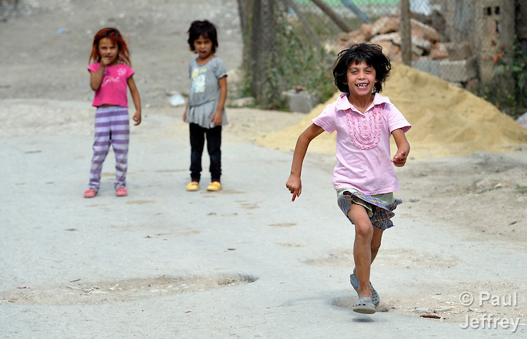 A girl runs down a street in a largely Roma, Turkish-speaking neighborhood of Dobrich, in the northeast of Bulgaria.
