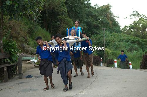 Kyaiktiyo. Porters carry two elderly women up the mountain to the Golden Rock November full moon ceremony. Burma Myanmar 2011.