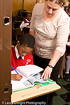 K-8 Parochial School Bronx New York Grade 4 female teacher leaning over to look at female student's work in class vertical