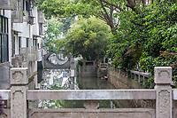 Suzhou, Jiangsu, China.  Small Canal Passing through Residential Section of Town.