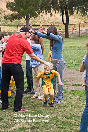 Caucasian elementary age boy in soccer uniform runs through human tunnel.after soccer game in Los Angeles park