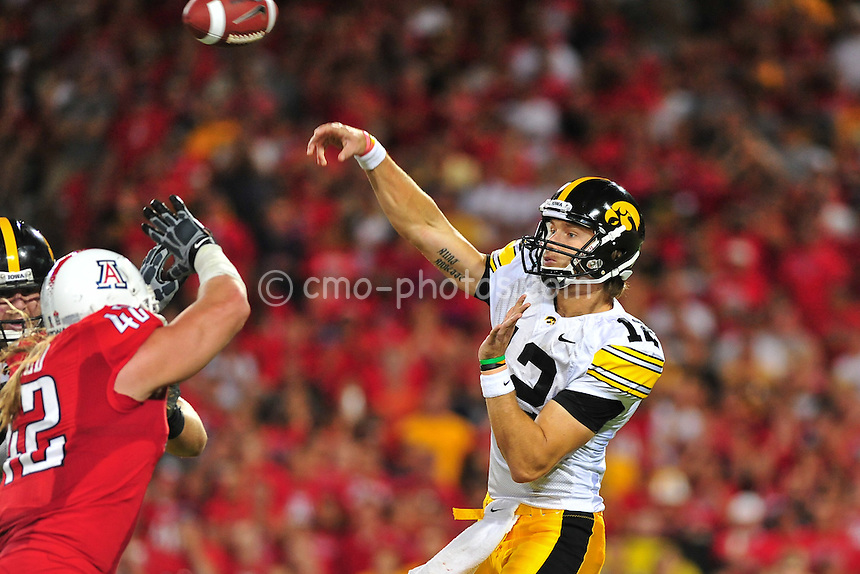 Sept 18, 2010; Tucson, AZ, USA; Iowa Hawkeyes quarterback Ricky Stanzi (12) throws a pass over the outstretched hands of Arizona Wildcats defensive end Brooks Reed (42) in the 1st quarter of a game at Arizona Stadium.