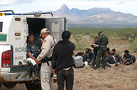 (From left) Isabel Orozco-Netzautal of Tlaxcala, Mexico (center) receives medical treatment for dehydration from Border Patrol Agent Johnny Bernac (left) and is comforted by her nephew, Vidal Netzautal-Meza (right), as other Border Patrol agents process other migrants in the Pima County Desert in Arizona, 23 miles north of the Mexican border on Monday, August 1, 2005. Orozco-Netzautal was traveling with a group of thirty that had been walking for four days before running out of water the night before. Border Patrol agents took her vital signs before giving her water, an electrolyte drink and an IV. She told the agents that she was surprised they were so kind to her, especially since Mexican television had often depicted them as abusive..