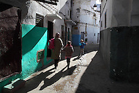 A woman and 2 children walking in a narrow street in the medina or old town of Tetouan on the slopes of Jbel Dersa in the Rif Mountains of Northern Morocco. Tetouan was of particular importance in the Islamic period from the 8th century, when it served as the main point of contact between Morocco and Andalusia. After the Reconquest, the town was rebuilt by Andalusian refugees who had been expelled by the Spanish. The medina of Tetouan dates to the 16th century and was declared a UNESCO World Heritage Site in 1997. Picture by Manuel Cohen