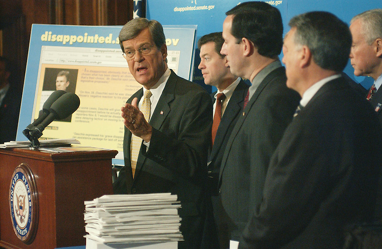 4/12/02.GOP VIEW OF STATE OF THE SENATE--Senate Minority Leader Trent Lott, R-Miss., Sen. Sam Brownback, R-Kan., Sen. Rick Santorum, R-Pa., Sen. Frank H. Murkowski (obscured), R-Alaska,  Sen. Jon Kyl, R-Ariz., and Sen. Orrin G. Hatch, R-Utah, during a news conference on the Republican leadership's view of the state of the Senate. Behind Lott is a poster of a web page accusing the Democratic leadership of delaying tactics on legislation..CONGRESSIONAL QUARTERLY PHOTO BY SCOTT J. FERRELL