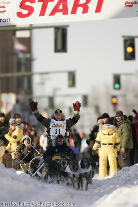 "March 3, 2007   4-time champion Jeff King runs down 4th avenue during the Iditarod ceremonial start day in Anchorage as his second sled handler takes a spill.  In the basket is ""Make-a-Wish"" rider Tim Rau"