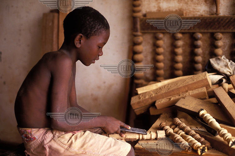 ©Giacomo Pirozzi/Panos Pictures..Sao Tome. Boy carving wood in furniture workshop.