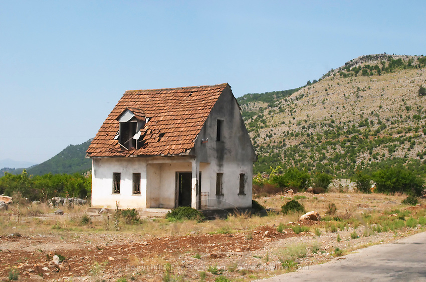 An abandoned house falling to pieces on the dry plain along the road between Shkodra and the Montenegro border. Albania, Balkan, Europe.